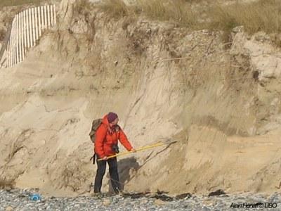homme décapant des sédiments suite à l'érosion des plages