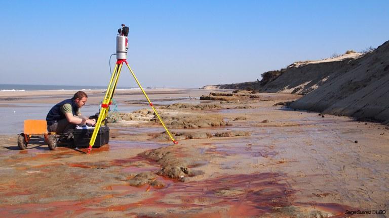 homme sur une plage qui prend des mesures à l'aide d'un scanner terrestre