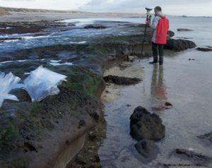 homme sur une plage avec affleurements de tourbe au sol